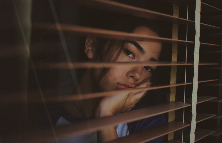 Brunette woman with hand under chin with low energy levels looks tiredly out her brown wooden blinds