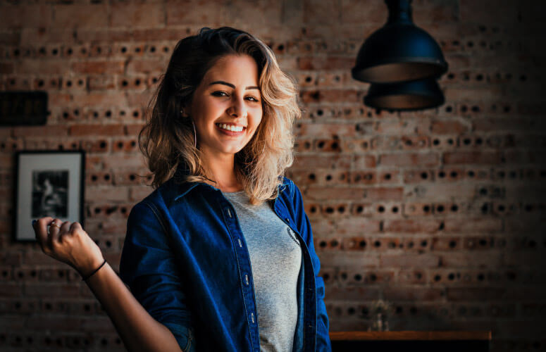 Blonde young woman wearing a denim jacket over gray shirt smiles in front of a indoor brick wall
