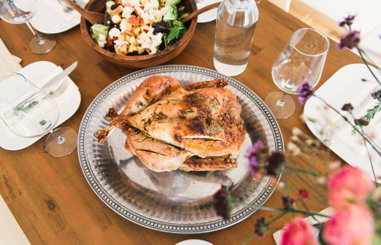 Aerial view of a Christmas turkey on a silver platter next to a holiday salad and water goblets